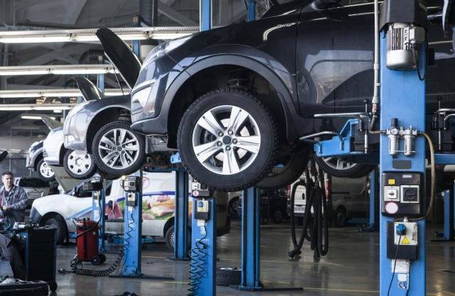 車検工場で車が整備されているシーン